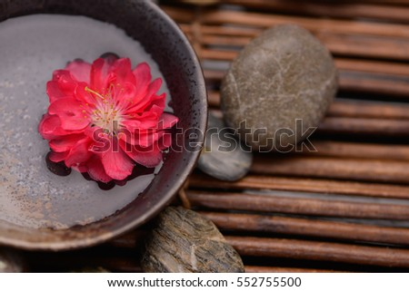 Red cherry flower in water bowl with stones, candle on mat