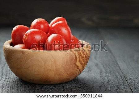 red cherry or plum tomatoes in wooden bowl, close up - stock photo