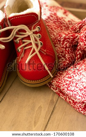 Red children winter shoes on the wooden background - stock photo