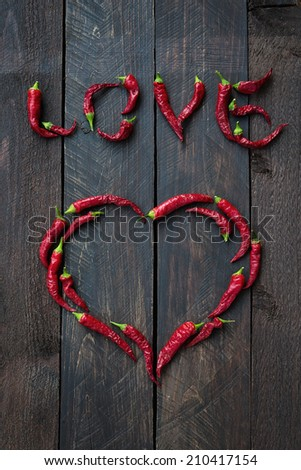 Red Chili pepper heart shape and Love word on wood aces background - stock photo