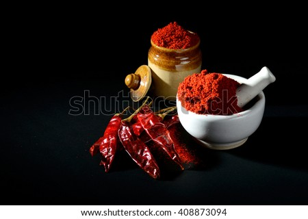 Red Chili Pepper powder in pestle with mortar and clay pot with Red Chili Peppers on black background - stock photo