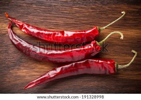 Red chili peppers on a wooden background. The menu background. - stock photo