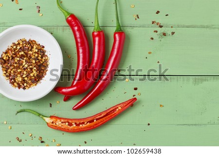 Red chili peppers on an old green board - stock photo