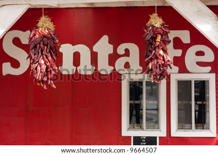 Red chilis hanging in front of an old Santa Fe railway carriage - stock photo