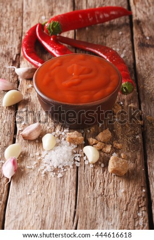 Red chilli sauce Sriracha with ingredients close-up on the table. vertical
