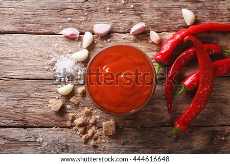 Red chilli sauce Sriracha with ingredients on the table. Horizontal view from above