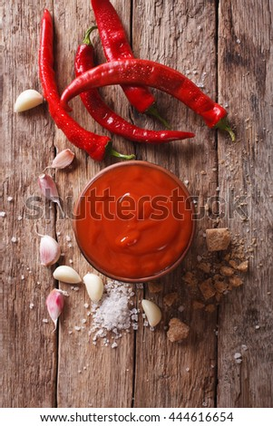 Red chilli sauce Sriracha with ingredients on the table. vertical view from above