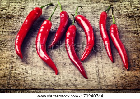 Red Chillies on Rustic Background - seven red chillies on a plank or rustic background, with an instagram effect. - stock photo