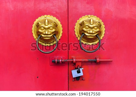Red chinese door with a lion hand door - stock photo