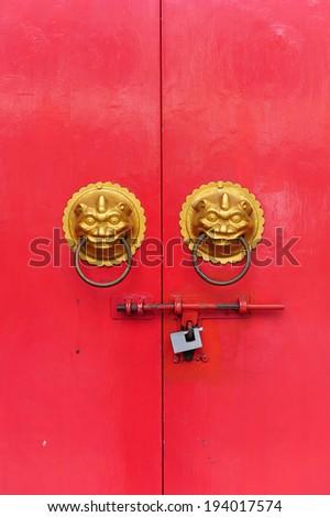Red chinese door with a lion hand door - stock photo