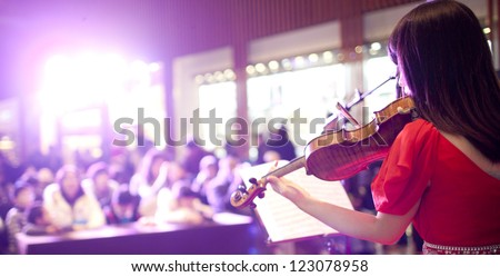Red Chinese girl playing violin in the super market for x'mas holiday - stock photo