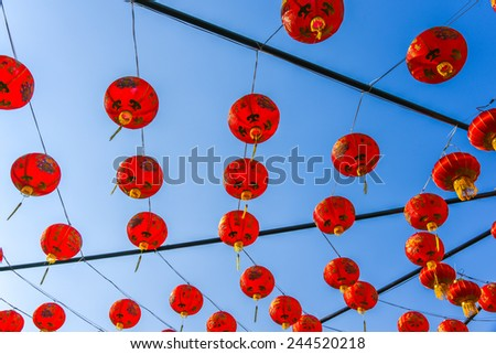 red Chinese paper lanterns hang in public for Chinese new year festival under blue sky - stock photo