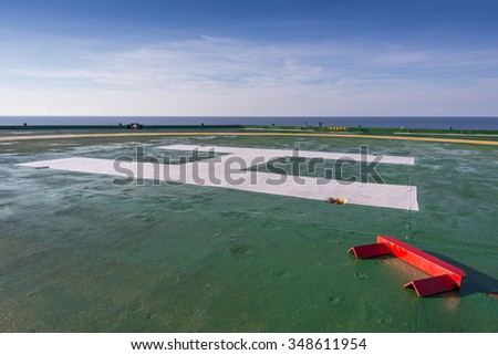 Red chock on the green oil rig helipad in Gulf of Thailand with blue sky - stock photo