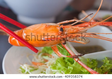 Red chopsticks holding a prawn with seafood sauce. - stock photo