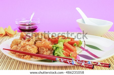 Red chopsticks in foreground of sweet and sour chicken dinner on bamboo place mat.
