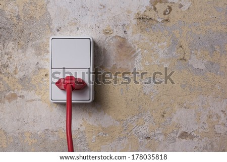 Red chord and plug in a white electrical socket on a worn brick wall - stock photo