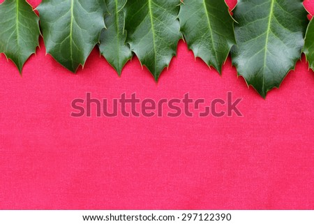 Red Christmas background with holy leaves - stock photo