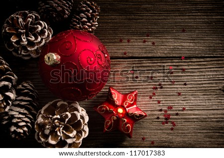Red Christmas ball and candle with pine cones on wooden top