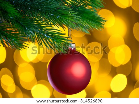 Red Christmas Ball and Green Fir Branch on the Blurred Background with Bright Yellow Holiday Lights. Christmass and New Year Decoration. - stock photo