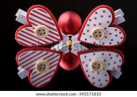 red christmas ball and heart clothespins reflected in a mirror with black background - stock photo