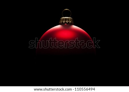 red christmas ball in tense light on black background