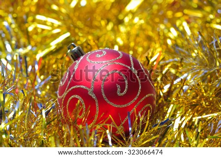 Red christmas ball in the golden tinsel defocused backgrounds - stock photo