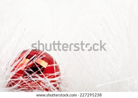Red Christmas ball on a white tinsel - stock photo