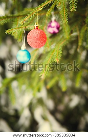 Red Christmas ball on fir-tree branch outdoor - stock photo