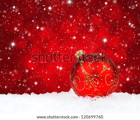 Red christmas ball on snow on a festive background - stock photo