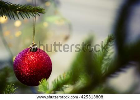red christmas ball on the green tree - postcard - stock photo