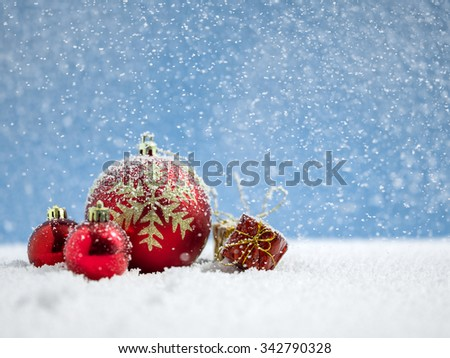 Red christmas ball with gift on snow