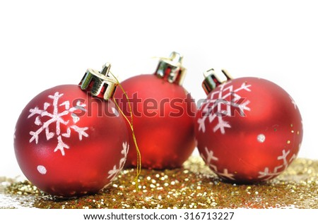 Red christmas balls and gold glitter on white background