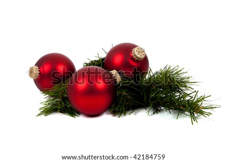 Red Christmas balls/baubles with a pine tree branch on a white background