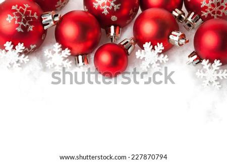 red christmas balls in the snow on white. studio shot - stock photo