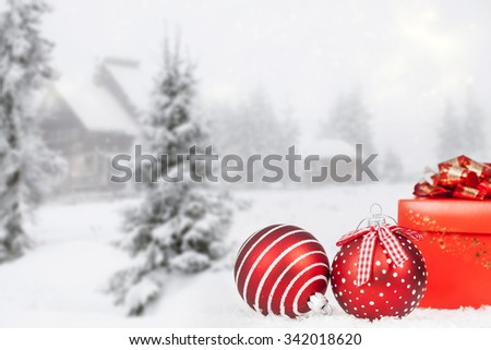 Red Christmas balls in the snow, snow cowered pine trees in the background - stock photo