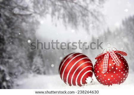 Red Christmas balls in the snow, snowy pine trees in the background - stock photo