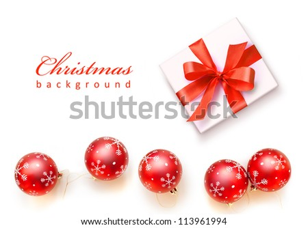 Red Christmas balls with snowflakes  and white gift with red ribbon bow, isolated on white background