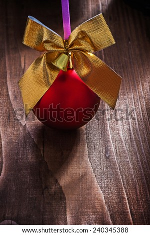 red christmas bauble and gold colored bow with small bell on old wooden board - stock photo