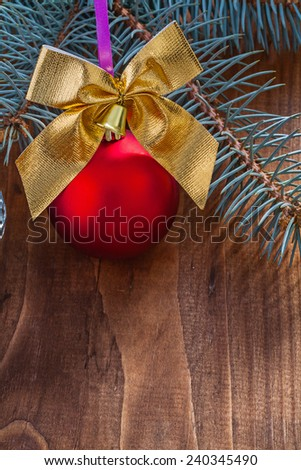 red christmas bauble and gold colored bow with small bell on old wooden board with pine tree branch - stock photo