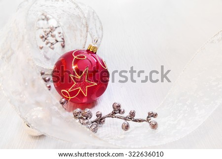 Red Christmas bauble with golden ornament on neutral winter background, text space. Shallow DOF, focus on the centre of the ball, space for your text - stock photo