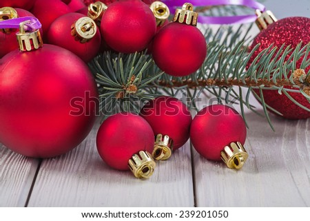 red christmas baubles and branch of pinetree on white boards - stock photo