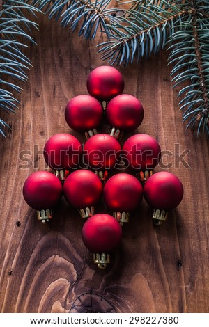 red christmas baubles in the form of fir tree and branches firtree vintage wood board. - stock photo