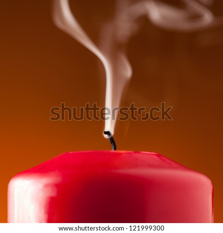 Red Christmas candle blown out on orange-red background - stock photo