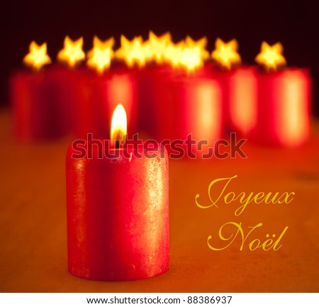 Red Christmas candle - with group of similar candles on background with stars for flames; with text Joyeux Noel, Merry Christmas in French