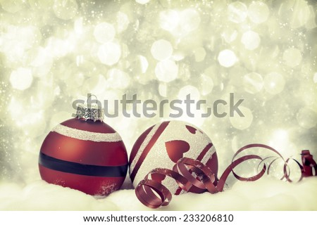 Red Christmas decorations in the snow, snow cowered pine trees in the background