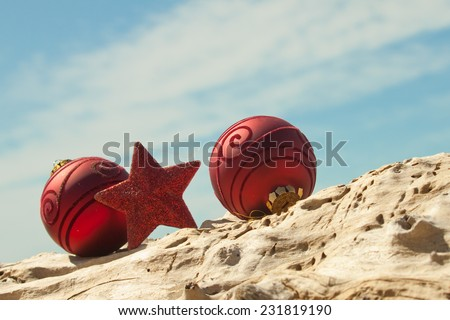 red Christmas decorations with sand and driftwood at a New Zealand beach  - stock photo