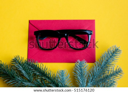 Red christmas envelope and style glasses on yellow background