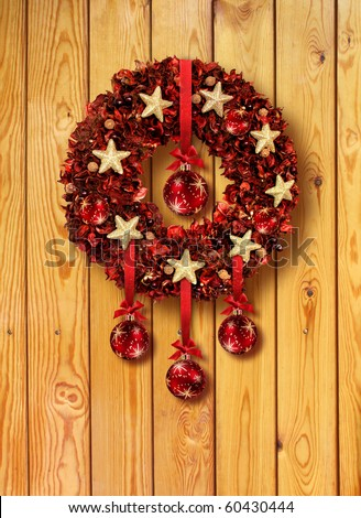 Red Christmas garland with glass balls on old wooden door