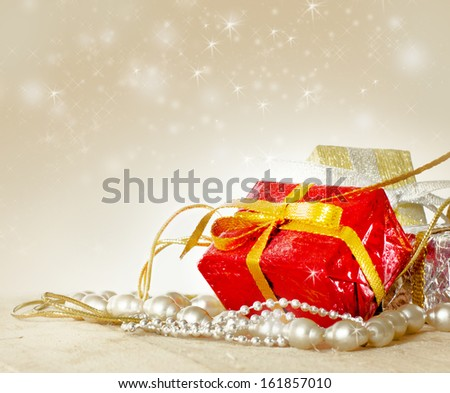 Red Christmas gift box and baubles on background of defocused golden lights. - stock photo