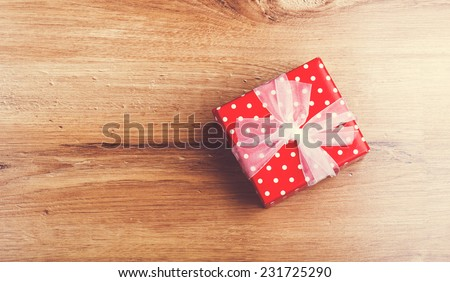 Red christmas gift box on wooden table - stock photo